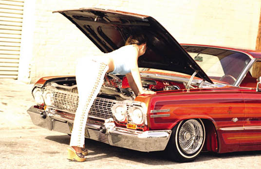 model working on a lowrider's engine